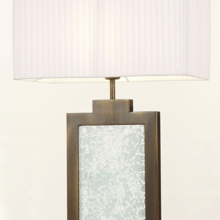 This lighting collection is characterized by Murano glass with murrine, a brown wooden base and burnished frame with a white organza plissé lampshade. Inspired by simple volumes, the preciousness is given by the white murrine inside the burnished
