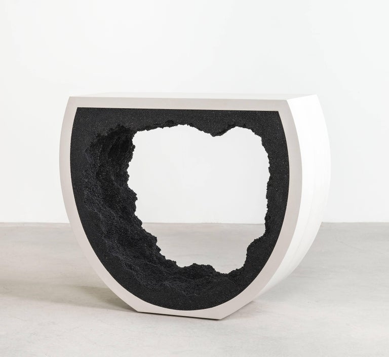 This console consists of a hand-dyed white cement exterior and a black silica interior. The silica is packed by hand within the cement in an organic nature.