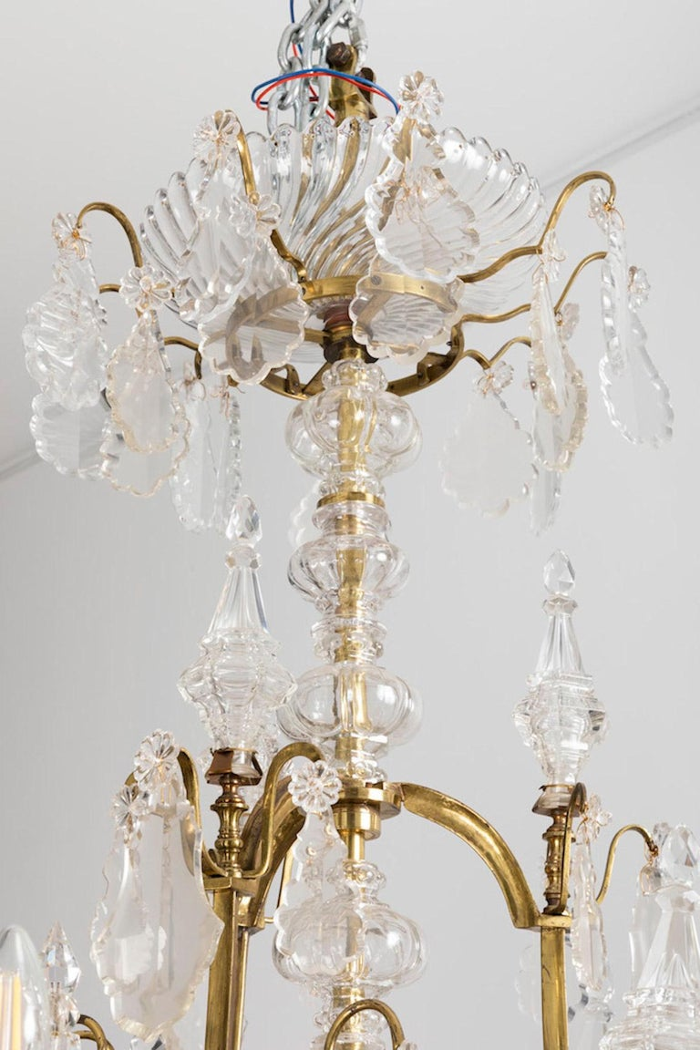 Baccarat, signed.  Large Louis XV style cage chandelier with 18 fires on two levels with a curved shaped gilt brass structure. Crystal cache-bélière (hide-hook) in a shape of a large twisted gadroons cup supported by a gilt brass circular ring on