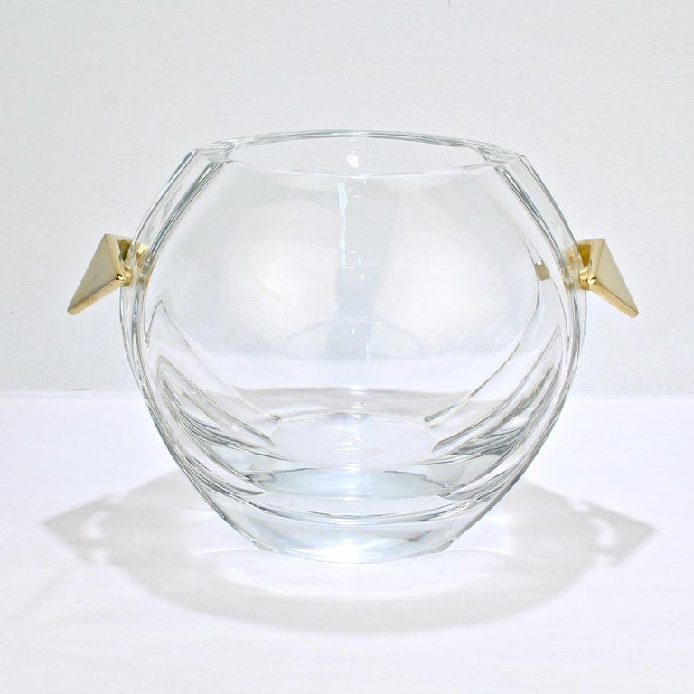 A fantastic midcentury Baccarat glass ice bucket.  With chevron shaped gilt bronze handles, a spherical body, and shaped sides.  Simply top quality design in very rare form from one of the world's leading glass houses!  The base bears an