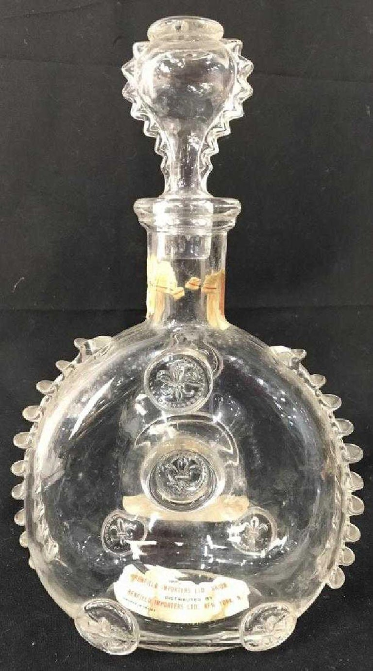 Vintage Baccarat Remy Martin Louis XIII crystal decanter bottle with stopper, decorated with fleur-de-lis medallions and ruffled edges or spiny trim. Designed to hold Grande Champagne Louis XIII cognac, the underside is acid-etched with the Baccarat