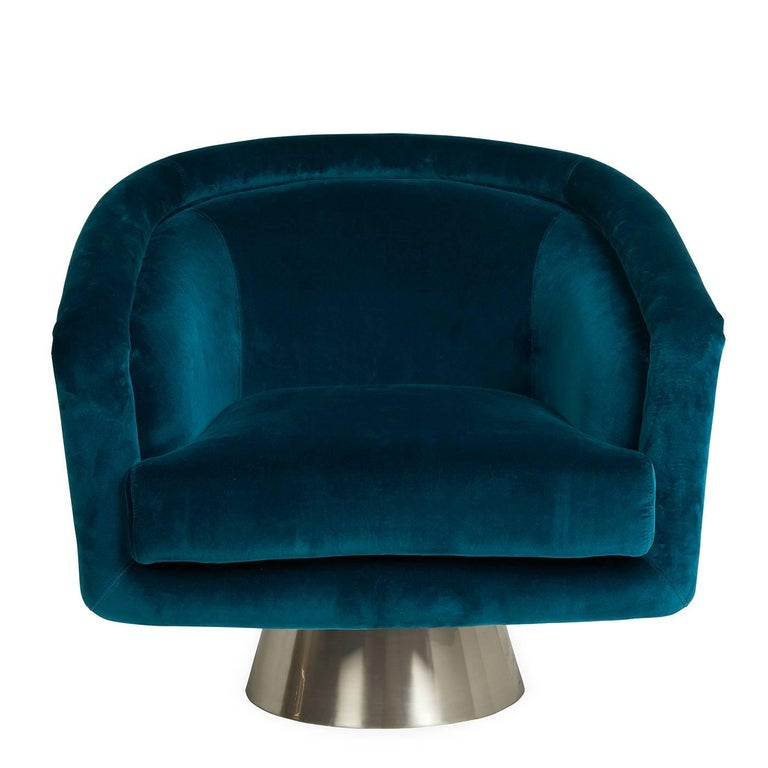 Louche glamour. Think Halston, think Studio 54, think sybaritic style. But also think cozy, comfy swivel chair. Upholstered in inky blue Lido Reef velvet with an architectural brushed stainless steel swivel base.  Specs: Seat depth: 20.5 in. Lido