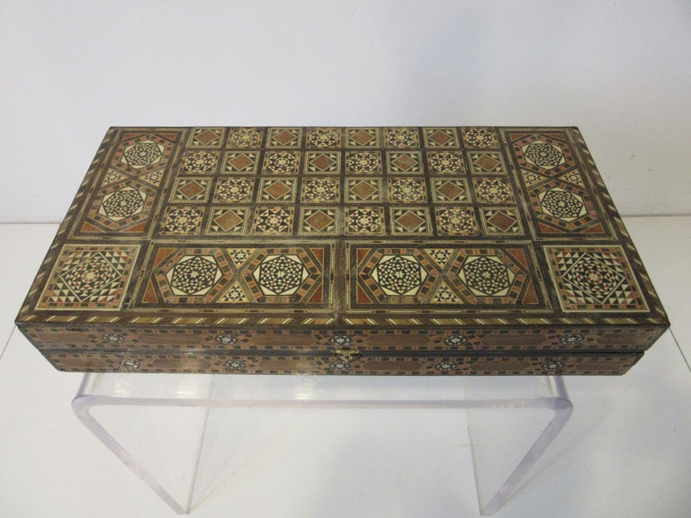 A handcrafted backgammon board with micro mosaic inlay using exotic wood, horn, bone and other items having Moorish motif designs. This hinged folding board is a piece of art and would be prized for it's craftsmanship and design covering both the