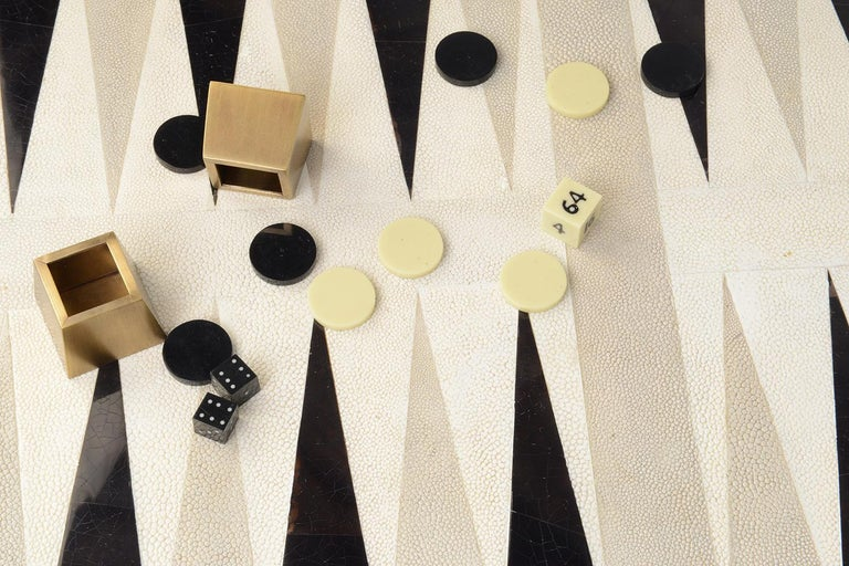 The KIFU PARIS Backgammon Game Tray is the ultimate luxury game. Accented with a mixture of shagreen, pen shell and bronze-patina brass this piece comes with all game parts in a velvet pouch. Available in a light or dark color-way.  The dimensions