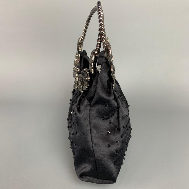 BADGLEY MISCHKA evening handbag comes in a black & silver beaded satin material featuring a silver tone metal top handles, silver tone floral details, and a inner pocket. Comes with dust bag.  Very Good Pre-Owned Condition.  Measurements:  Length: 9