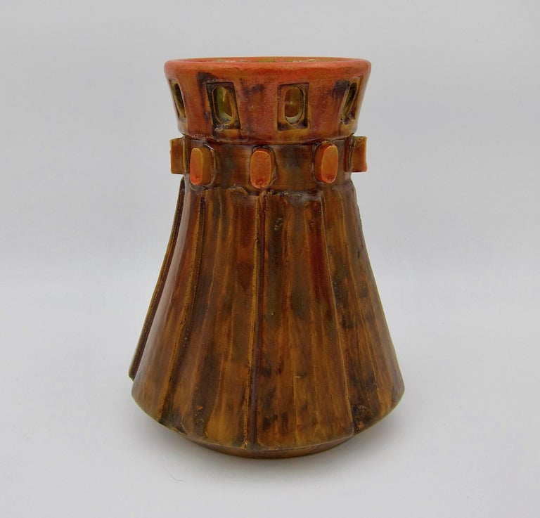 A midcentury Raymor vase designed by Alvino Bagni for Bagni Ceramiche of Italy, dating circa 1960s. The sculptural Italian Modern art pottery vessel is wheel thrown and features a pierced upper rim over a collar of applied cog-like projections and a