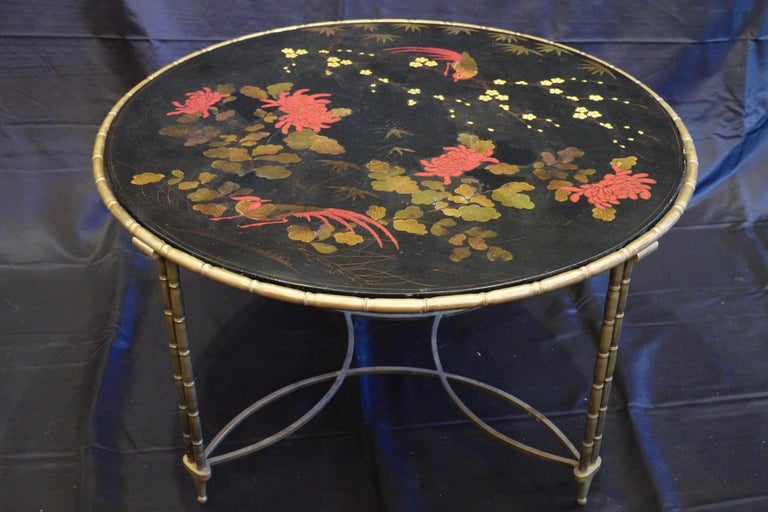 Lovely French round cocktail or coffee table with colorful Japanned lacquered top surface in black ground, featuring red birds and peonies, yellow flowers and bamboo leaves. The frame of the table is nicely-cast faux bamboo in bronze, supported by