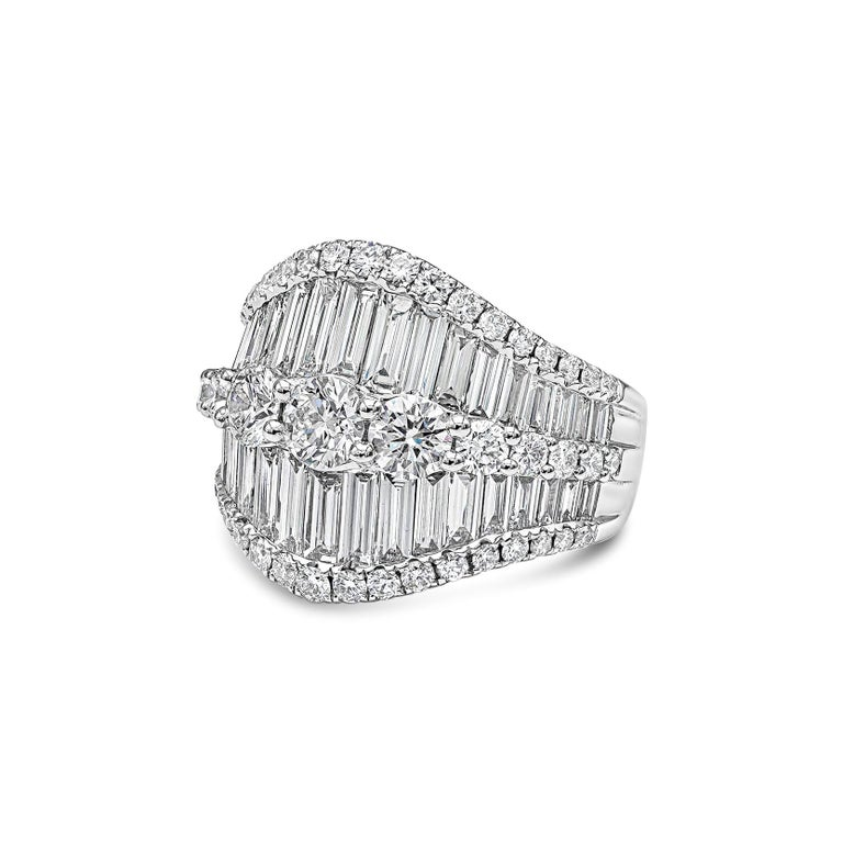 A brilliant and unique piece of jewelry showcasing a row of graduating round diamonds, set in between graduating baguette diamonds. Finished with small melee diamonds on both sides of the ring. Baguette diamonds weigh 2.50 carats total; round