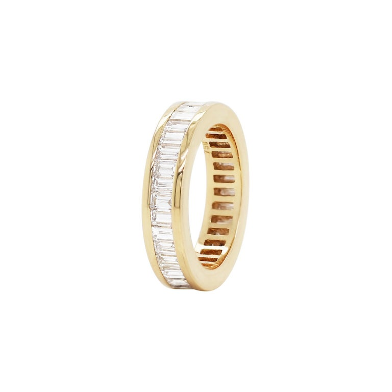 Beautiful eternity ring channel set with 36 fine quality baguette cut diamonds with a total approximate weight of 3.00ct, all mounted in 18ct yellow gold. The ring weighs 7.6gr and measures 5.2mm. Stamped 750. UK finger size 'N'.