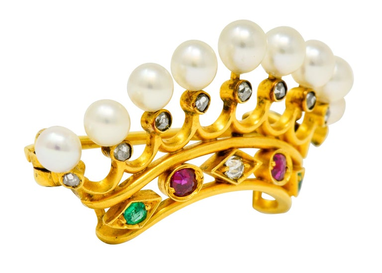 Brooch is designed as a pierced crown with each tine as a scalloped fishtail motif accented by rose cut diamonds  Each tine is topped by a round pearl, measuring from 3.3 to 3.5 mm, and are a well-matched cream body color with excellent