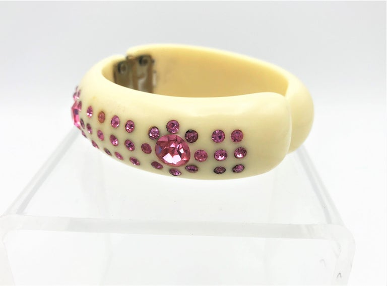 Very nice ivory colored bangle set with pink rhinestone and with hinge to open.   Measurement: Width 2 cm inside, outside 3 cm, inner circumference 17 cm, the 2 pink strass stones are 1 cm diameter. Very good condition, no missing rhinestones. The