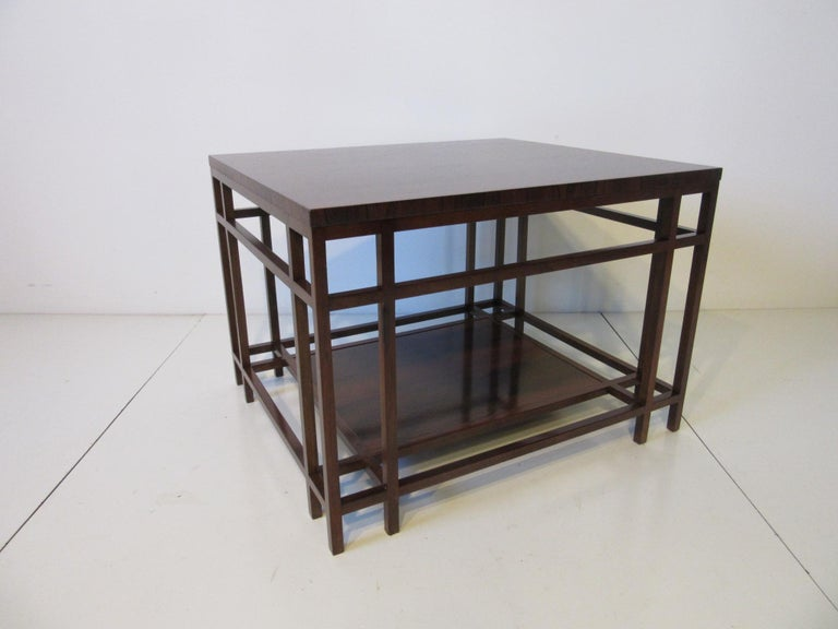 A well grained deep rich Brazilian rose wood side or end table with architectural styled base and shelve , retains the metal label manufactured by the Baker Furniture company . A well crafted piece of furniture which is typical for Baker.