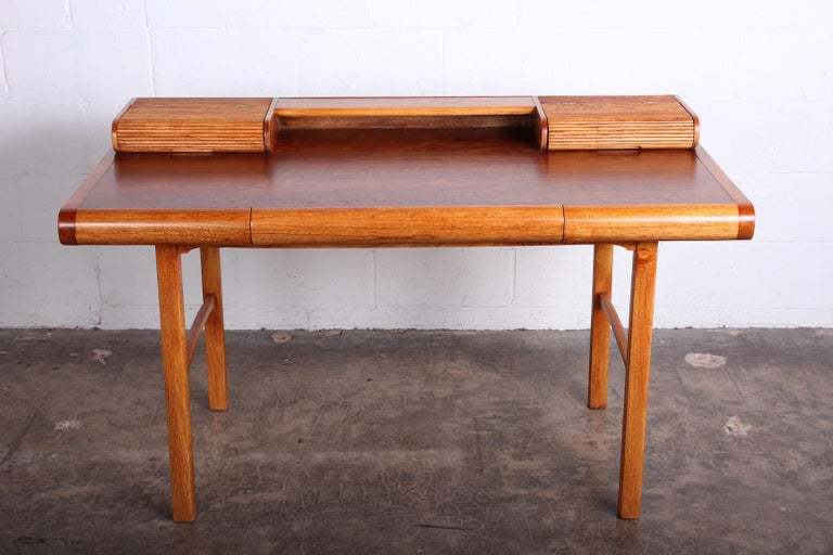 A nicely detailed petite desk by Baker. Oak and walnut with hinged compartments at top.  Desktop height 28.75