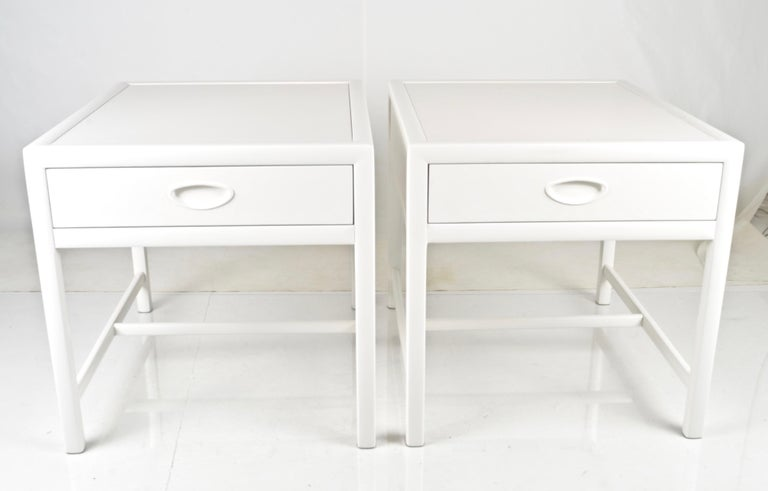 Classic modern single-drawer end tables or bedside tables made by Baker Furniture in the 1950s. Now restored with a new satin lacquer finish in dove white. Note: back is fully finished allowing tables to be floated if desired. Quality construction.