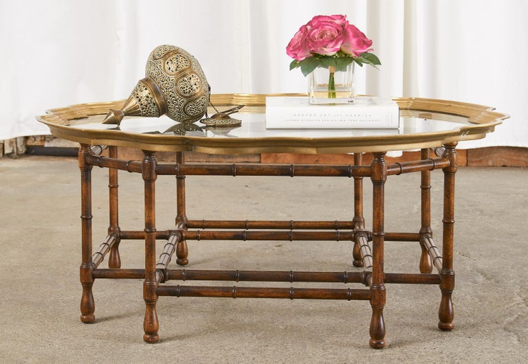 Hollywood regency brass and glass tray top coffee or cocktail table with dramatic scalloped edges framing the pane of glass. The mid-century modern table has a geometric octagonal shaped faux bamboo wood base with a beautiful open design. The tray
