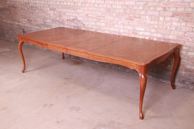 An exceptional French Provincial Louis XV style extension dining table  By Baker Furniture  USA, circa 1960s  Cherrywood, with parquet top.  Measures: 67.75