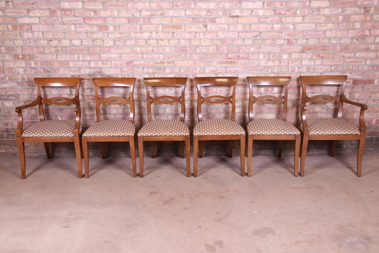A gorgeous set of six French Provincial dining chairs  By Baker Furniture  USA, mid-20th century  Solid walnut frames, with upholstered seats.  Measures: Side chairs- 19.25