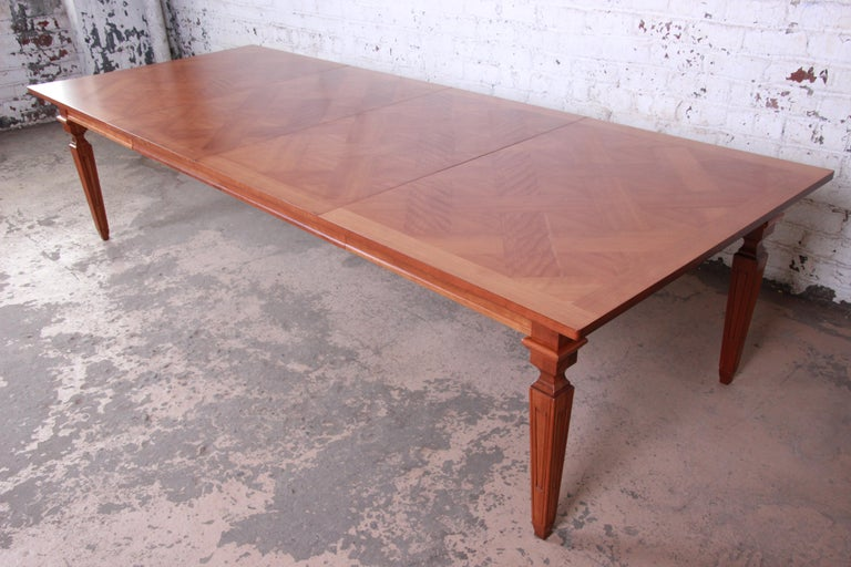 A gorgeous newly restored French Regency extension dining table by Baker Furniture. The table features a nice parquetry top and beautiful cherrywood grain. With two large 26.5