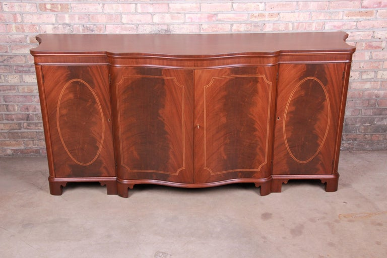 An exceptional Georgian style sideboard buffet or bar cabinet  By Baker Furniture  USA, circa 1950s  Flame mahogany, with pencil inlay. Cabinet doors lock, and original key is included.  Measures: 78