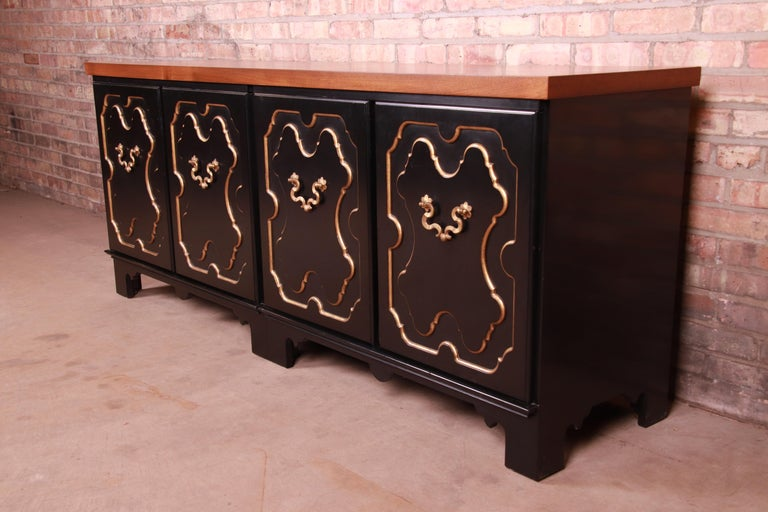 A gorgeous mid-century Hollywood Regency Chinoiserie sideboard credenza or bar cabinet  By Baker Furniture  USA, Circa 1960s  Book-matched walnut top, with black lacquered case having gold gilt trim and original brass hardware.  Measures: