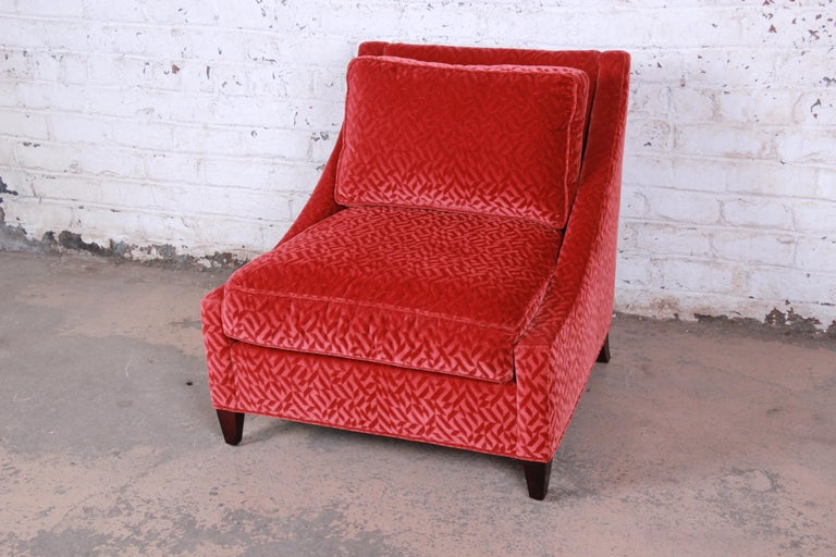 A gorgeous modern lounge chair by Baker Furniture. The chair features sleek modern lines with solid mahogany legs and beautiful red velvet upholstery. It is very plush and comfortable. The original Baker label is present. The chair is in excellent