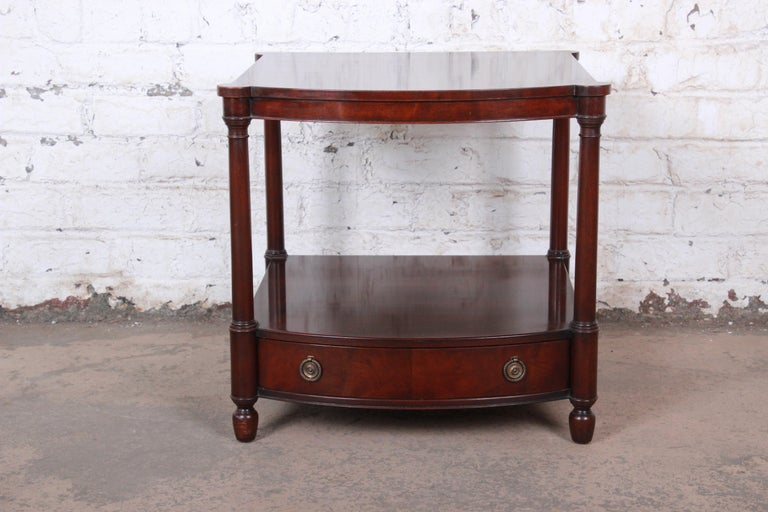 A gorgeous English traditional style mahogany occasional side table or nightstand  By Baker Furniture  USA, circa 1950s  Mahogany and brass hardware  Measures: 24