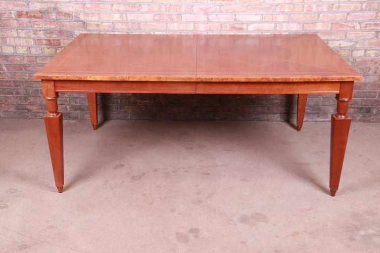 A beautiful Neoclassical style extension dining table  By Baker Furniture,  USA, circa 1990s  Book-matched inlaid cherry wood, with burl wood banding.  Measures: 70