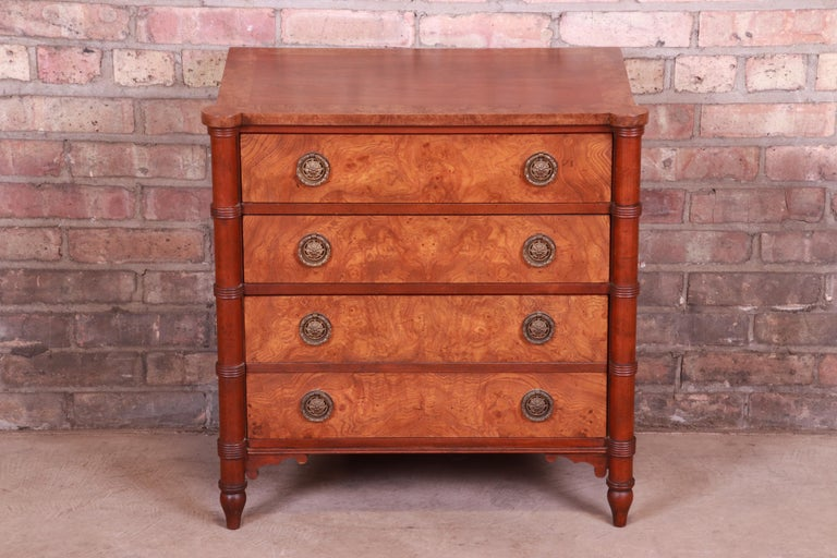 An exceptional Regency style bachelor chest or nightstand  By Baker Furniture  USA, 20th century  Book-matched walnut, with burled walnut banding and drawer fronts and original brass hardware.  Measures: 24.5