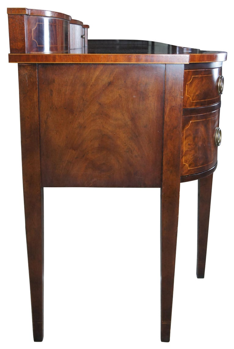 Baker Furniture Sheraton style mahogany serpentine sideboard buffet hepplewhite.  Monumental Baker Furniture serpentine sideboard. Made of mahogany with flame mahogany drawer fronts and inlaid accents. Features five drawers with brass hardware and