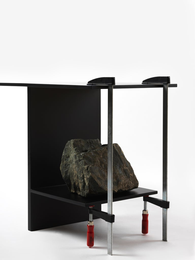 Balance table by Lee Sisan 2019 Dimensions : W 130 x D 45 x H 65 cm Materials : Powder Coated Steel, Natural Stone  Each piece is made to order and uses natural stones, so please expect some variability in design.  The clamp, the iron plate,