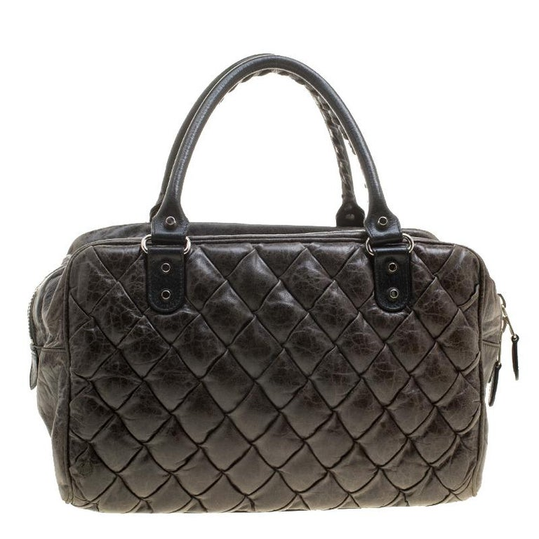 Super functional and modish, this Balenciaga satchel is a serious style elevator. It is crafted with Chevre leather featuring quilted pattern. It comes with a tasseled front zip pocket, a spacious interior lined with fabric, and double top handles