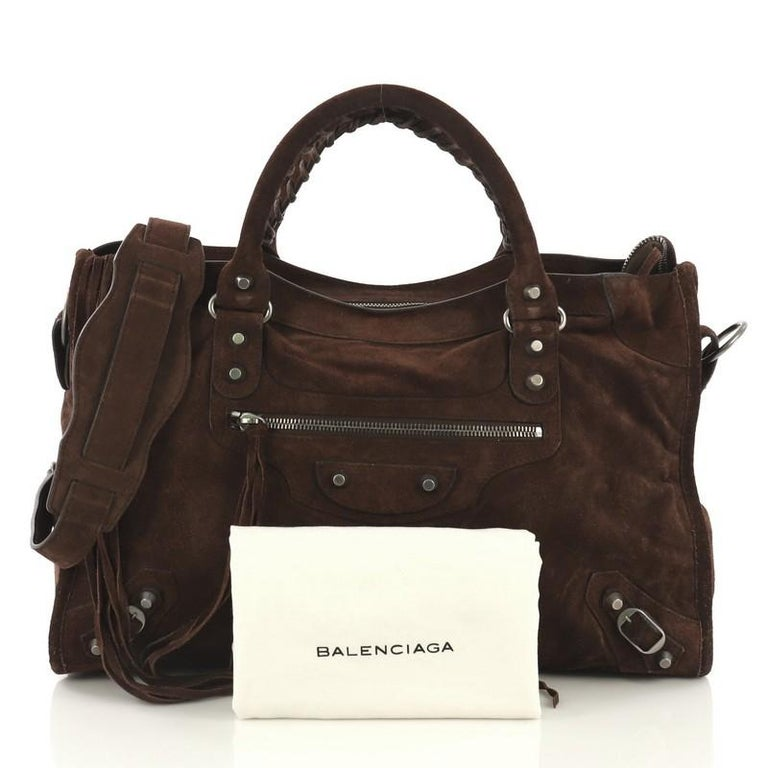 This Balenciaga Baby Daim City Classic Studs Bag Suede Medium, crafted in brown suede, features a front zip pocket and accented with braided hand-stitched handles, iconic Balenciaga classic studs and buckle details, and gunmetal-tone hardware. Its