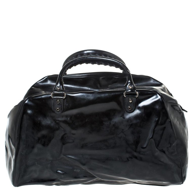 This Balenciaga Bowling bag is simply inimitable in its plush and modern design. The most attractive feature is its classic black color which enhances its appeal. It is crafted from patent leather and features a smooth exterior. It flaunts dual top