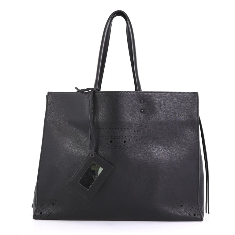 This Balenciaga Blackout A4 Zip Around Tote Leather Large, crafted in black leather, features slim handles, zip sides that allows the bag to expand, and aged gold-tone hardware. It opens to a black leather interior with zip pocket.   Estimated