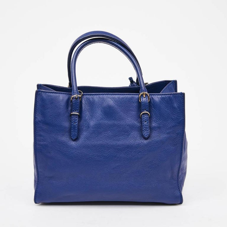 This mini A4 Balenciaga Paper is in blue leather. It can be carried by hand thanks to its two leather handles (adjustable) or crossover with its removable strap. The bag closes with a magnet, the interior is in blue suede with a small flat pocket.