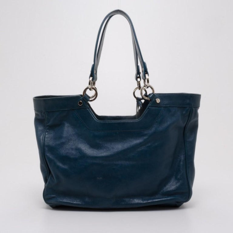 Stand out in a crowd with this sleek and modern Sac Clous handbag by Balenciaga. Crafted from teal leather, the exterior is perfectly accented with center metal detailing, two zip pockets and double handles. The large black canvas lined interior