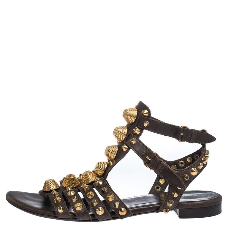 These stunning sandals by Balenciaga will make a statement. Crafted from leather, they come in brown. These gladiator style sandals feature straps embellished with gold-tone studs, buckle closure, and leather soles. They are stylish, edgy and