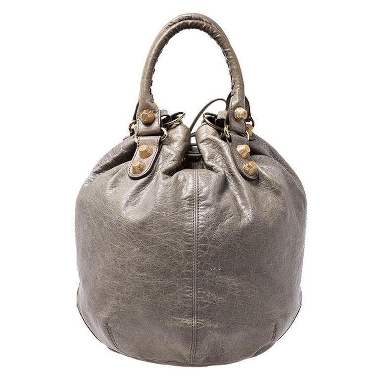 This Balenciaga 'Pompon' hobo bag will become your favorite daytime wardrobe addition! It is crafted from green leather and accented with signature gold-tone metal studs and other hardware details. The exterior is accented with a rolled top handles,