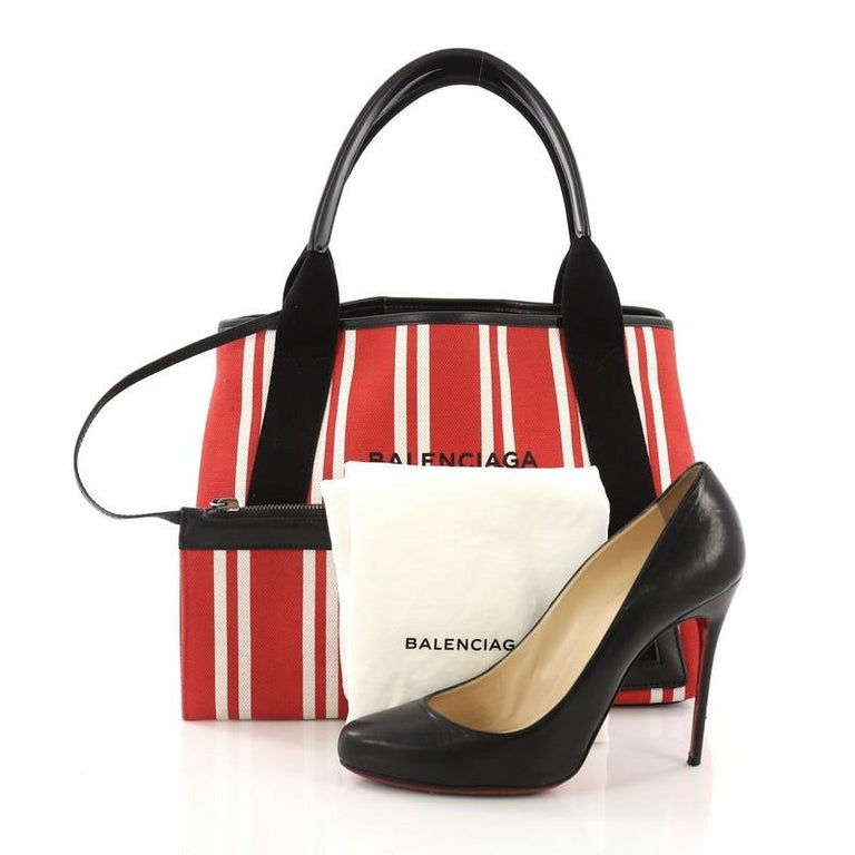 This Balenciaga Navy Cabas Canvas with Leather Small, crafted in red and white striped canvas, features dual leather handles, stamped Balenciaga Paris logo, and silver-tone hardware. It opens to a matching off white canvas interior. **Note: Shoe