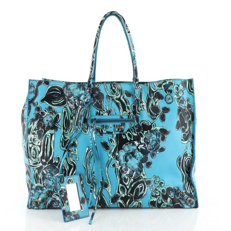 This Balenciaga Papier A4 Classic Studs Bag Printed Leather Medium, crafted in blue printed leather, features dual slim handles, front zip pocket, studs and buckle details, and aged silver-tone hardware. It opens to a neutral suede interior with
