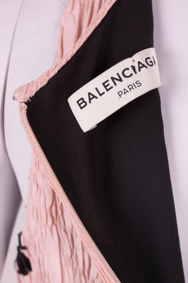 A perfect and body-contouring dress by Balenciaga Paris covered with black flower appliques. Picture perfect!  This sleeveless dress has a scoop neckline and concealed zip closure on the back. Crafted in a very pale pink and crinkled silk