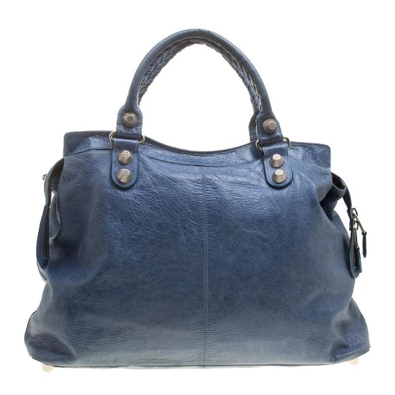 This Balenciaga RTT bag is perfect for everyday use. Crafted from leather in a gorgeous sky blue hue, the bag has a feminine silhouette with two top handles and gold-tone hardware. The zipper closure opens to a fabric-lined interior and the bag is