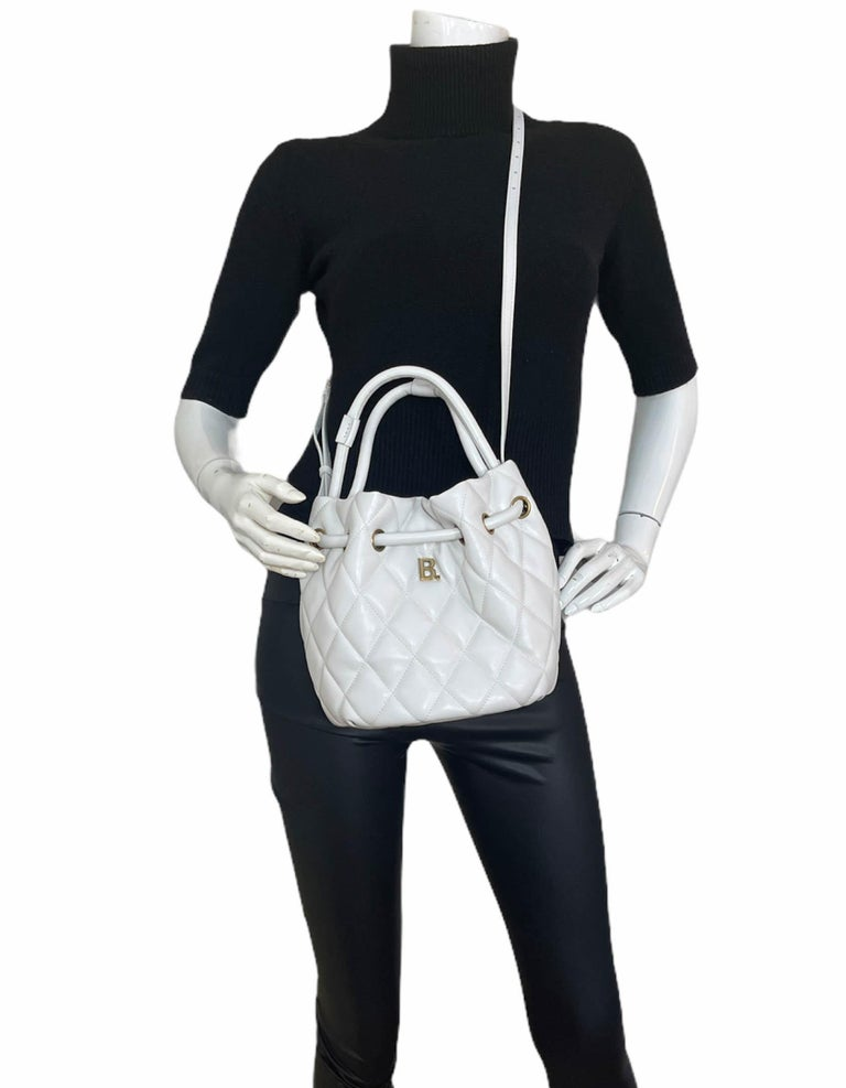 Balenciaga White Leather B Dot Quilted Bucket Crossbody Bag.  Features optional crossbody strap.  Made In: Italy Color: White Hardware: Antiqued goldtone Materials: Nappa calfskin leather Lining: Black fine textile Closure/Opening: Drawstring