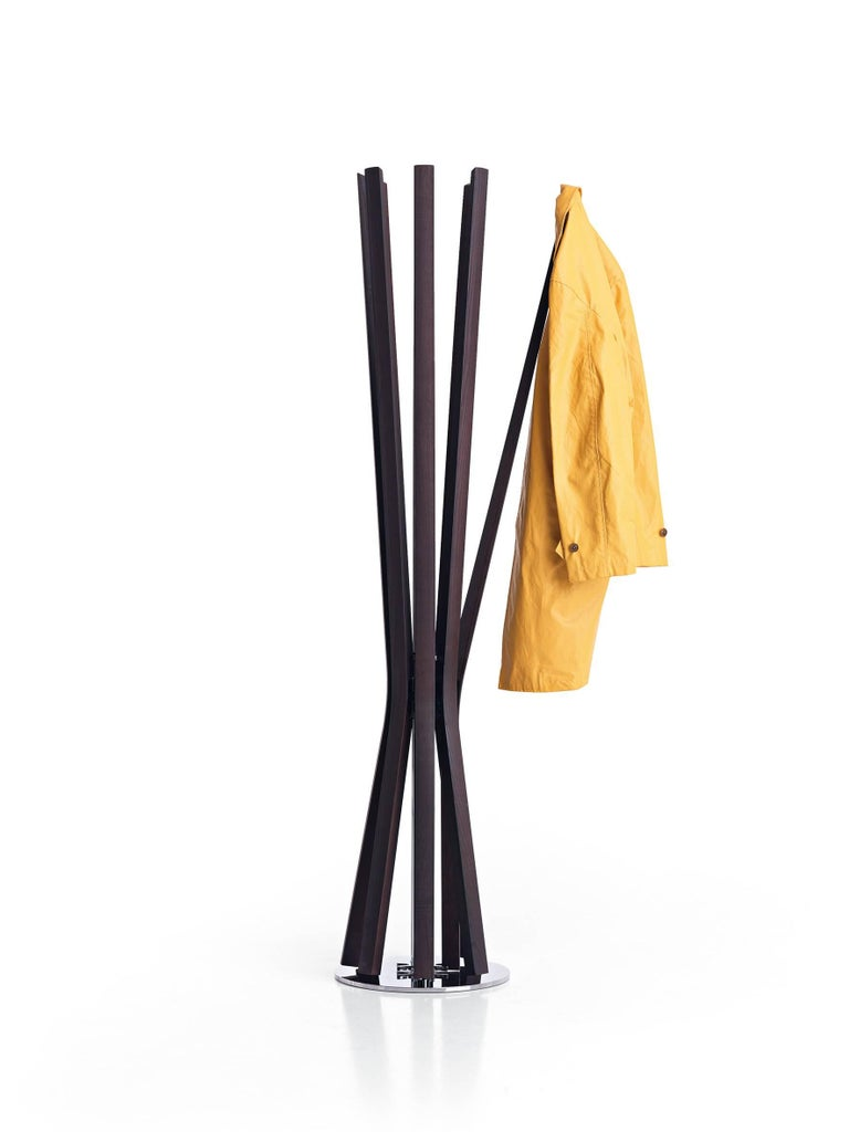 Coat-hanger with chrome steel structure and eight arms made of moka ashwood. The Bloom coat hanger can rotate around the central stem allowing easy access to each of the arms which open individually when weighted with a coat and close when clothing