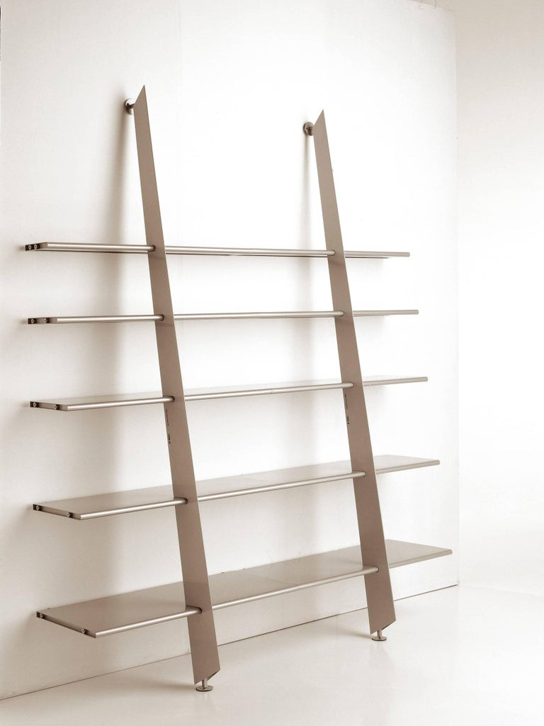 Modular bookshelves in steel sheet with epoxy finish in semi-glossy metallic silver. A central upright structure supports five shelves of decreasing depths.