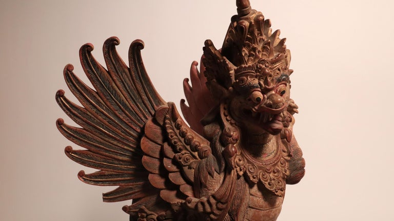 A tour-de-force from a master Balinese sculptor, with amazing detail, carved in very hard, dense wood. A winged lion (called a singha) temple or palace guardian. Bali, Indonesia. Expertly carved wood with paints, 20th century. It would have been