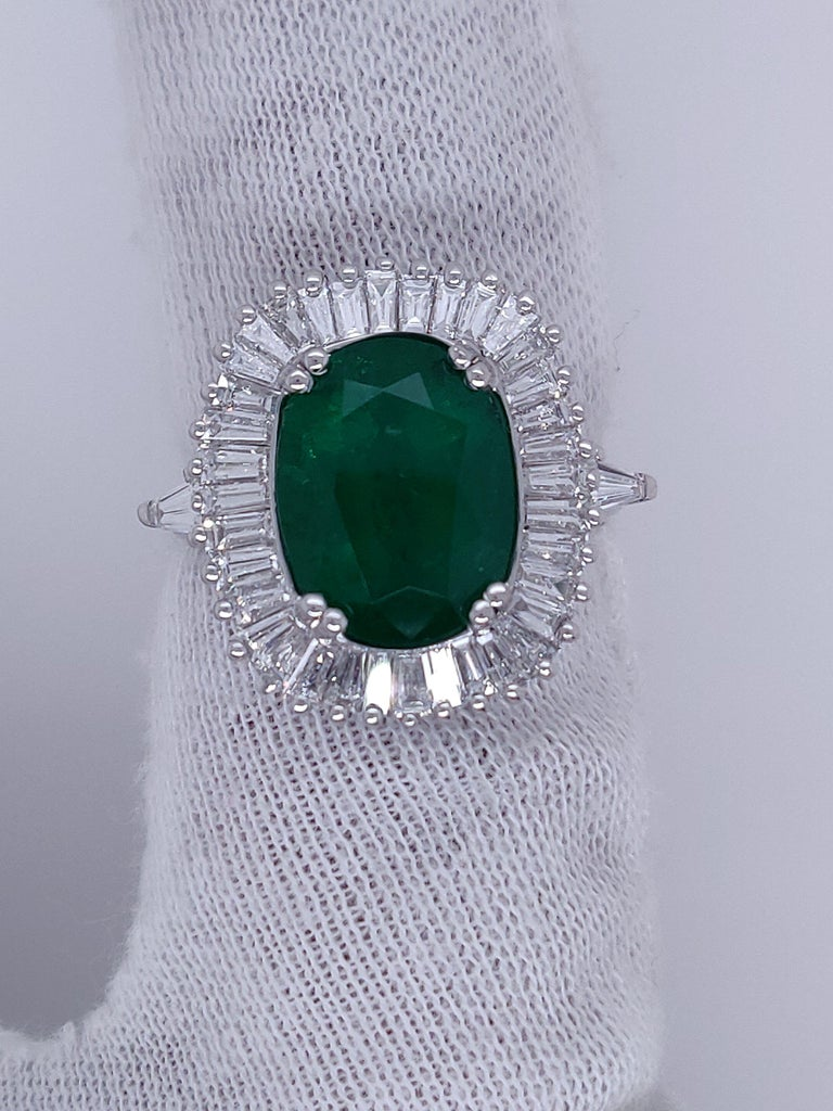 Hand Crafted Ballerina Style ring featuring an oval 4.32 Carat Natural Green Emerald as a center stone and accompanied by 38 high quality tapered baguette shaped diamonds 1.77 Carat TDW.  Our magnificent ring is made with precise detailed