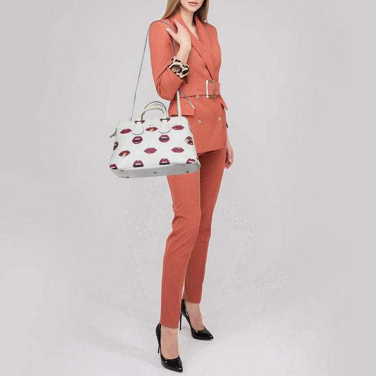 This playful Bally Berkeley tote flaunts a quirky lip print all over. Elegantly structured from leather, this creation is styled with dual handles. The top zip closure opens to fabric-lined compartments and pockets. The engraved plaque adds to the