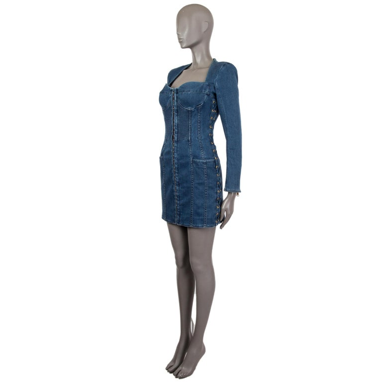 Balmain long-sleeved mini dress in indigo wash cotton (96%) elastane (4%) with zipped cuffs, lace-up panel at the sides and slit pockets at the hips. Featuring a bustier with a front panel hook and eye fastening, seam details, gold-tone hardware.