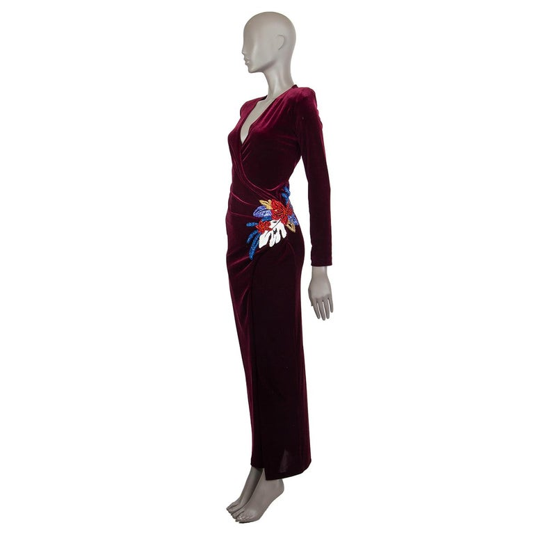Balmain velvet wrap gown in burgundy polyester (92%) and elastane (8%). With shoulder pads, long sleeves, low decollete, glass embroidery on the side of the waist, and high slit in the front side. Closes with gold-tone button on the back. Unlined.